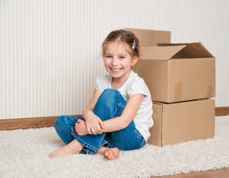 Little girl moving into new house, siting near boxes Foto de archivo