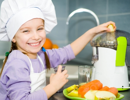 smily little girl making fresh apple juice with a juice extractor photo