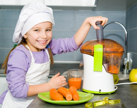 little girl making carrot juice with a juice extractor photo