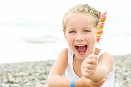 cute little girl with a candy on tropical beach vacation