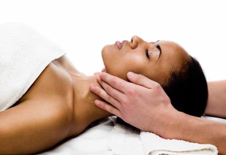 massaggio collo: giovane donna che riceve il massaggio del viso con gli occhi chiusi in un salone spa