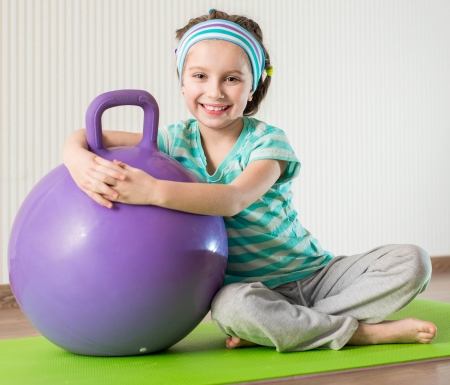 smiling girl with the fitness ball at home photo