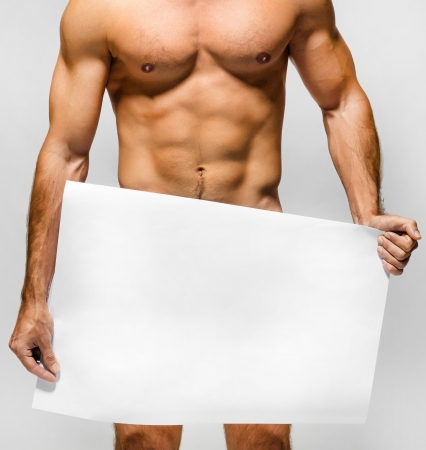 naked man: Naked muscular man covering with a banner  copy space  isolated on white Stock Photo