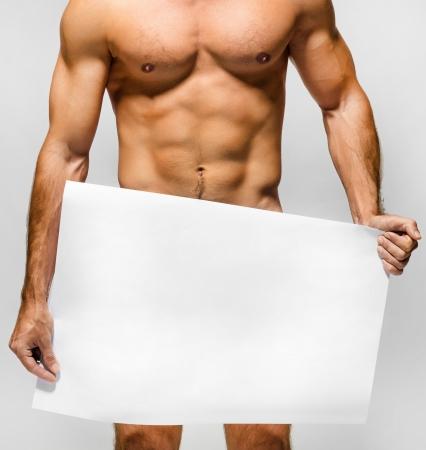 uomo nudo: Nudo uomo muscoloso che copre con un banner copia spazio isolato su bianco