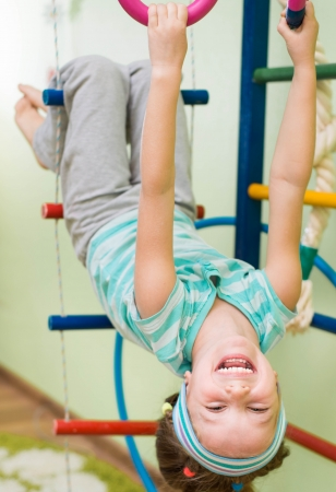 little girl playing at gymnastic rings photo