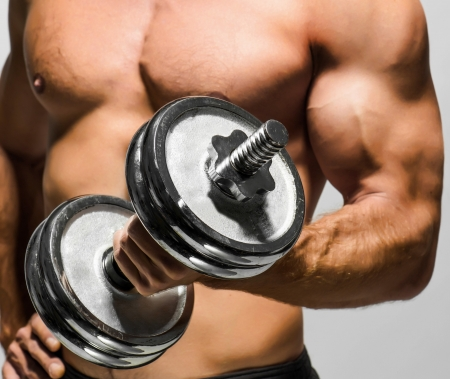 dumbells: Handsome muscular man working out with dumbbells