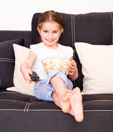 little girl holding popcorn and watching TV photo