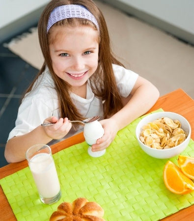 smiling little girl eating egg in the kitchen photo
