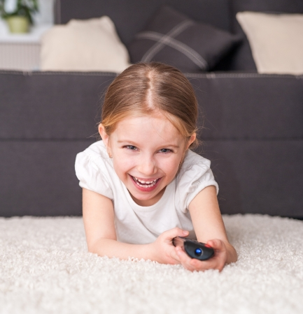happy little girl holding a remote control photo