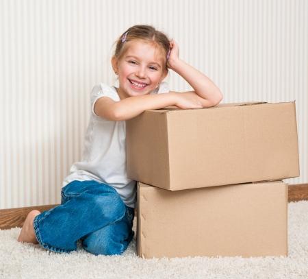 Little girl siting near cardboard box