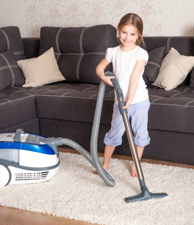 household chores: little girl cleaning the room - using vacuum cleane