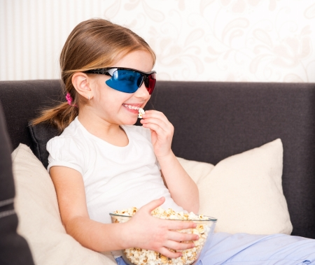pretty little girl holding popcorn and watching 3d TV photo