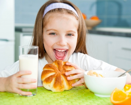 cute little girl eating a muffin in the kitchen
