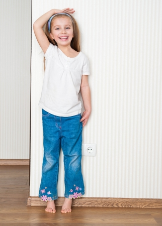 measure height: little girl measures the growth near the wall at home Stock Photo