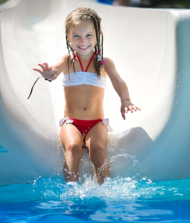 Little girl on water slide at aquapark  Summer holiday