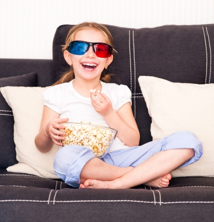 little girl in 3D glasses eating popcorn and watching TV photo
