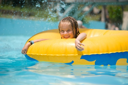 float tube: Little girl on inflatable ring in swimming pool
