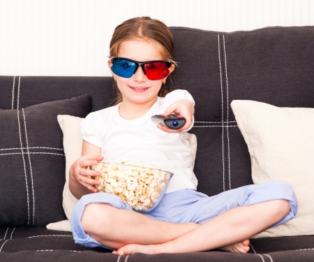 little girl with popcorn in 3D glasses holding a remote control watching TV photo
