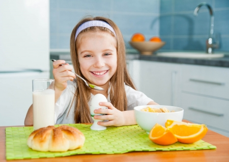 cute little girl eating egg in the kitchen