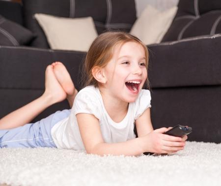 viendo television: linda niña sosteniendo un control remoto Foto de archivo