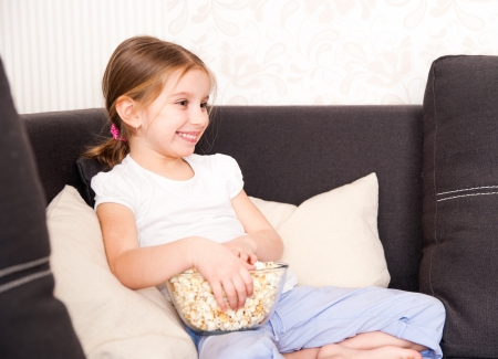 smiley little girl holding popcorn and watching TV photo