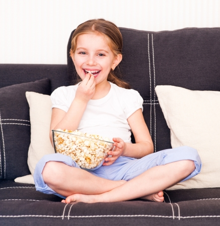 little smiley girl eating popcorn in front of TV photo