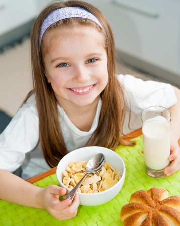 cute smiling little girl eating her breakfast in the kitchen