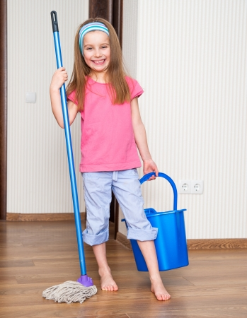 housecleaning: happy little girl washing the floor with a mop at home Stock Photo