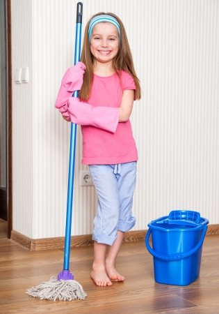 happy cute girl washing the floor with a mop at home photo