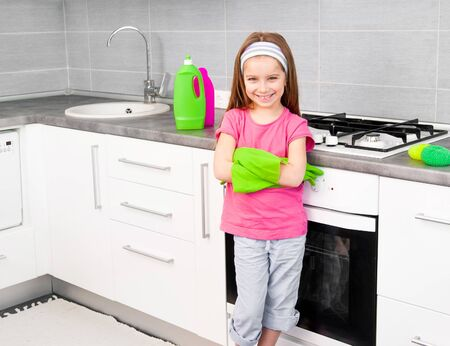 portrait of cute little girl cleans in the kitchen at home photo