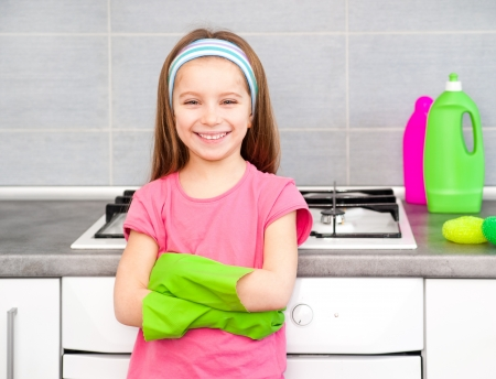 little girl cleans in the kitchen at home photo
