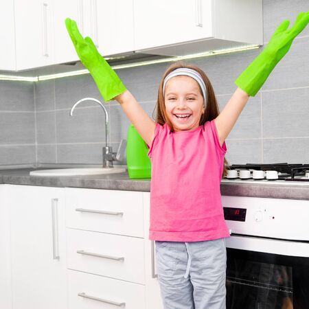 portrait of happy little girl cleans in the kitchen at home photo