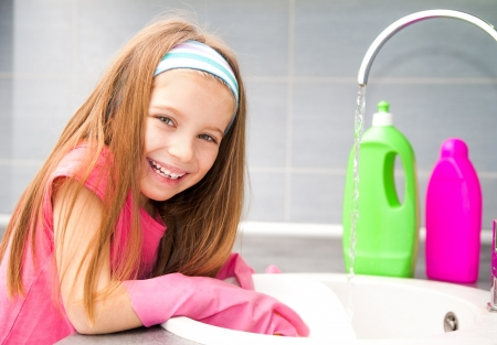 pretty little girl washing the dishes in the kitchen photo