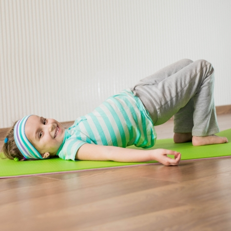 smiling little girl engaged in fitness at home photo