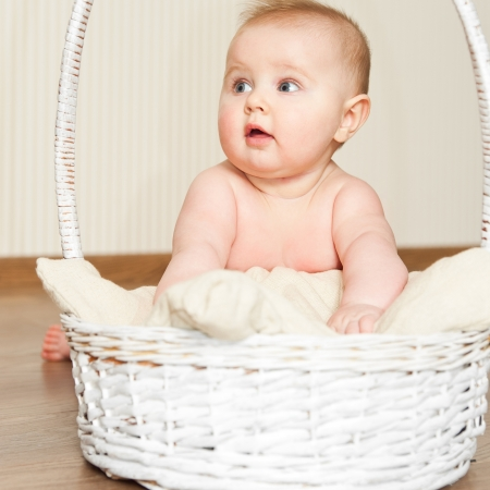 Adorable baby girl in wicker basket photo
