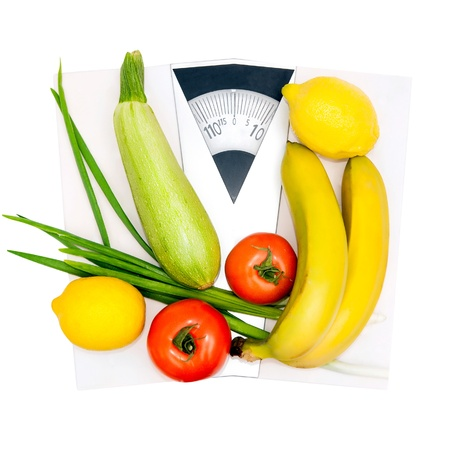 Diet and nutrition  Vegetables and fruits on the scales photo