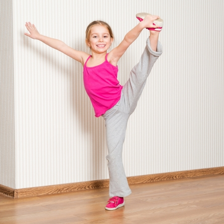 pretty little girl in pink engaged in fitness at home