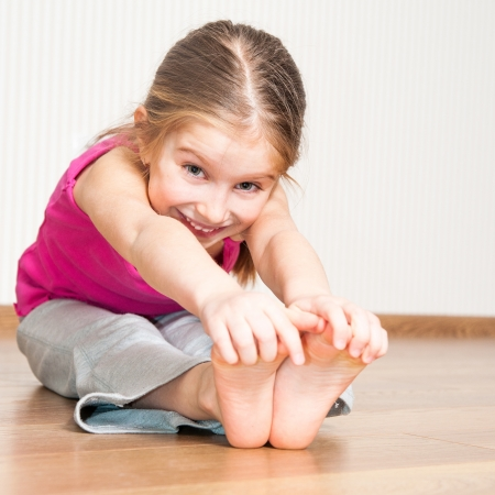 smiling little girl in pink engaged in fitness Stock Photo