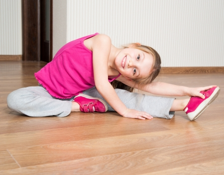 smiling little girl in pink engaged in fitness at home Foto de archivo