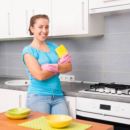 young smiling cute woman cleans the kitchen at home photo