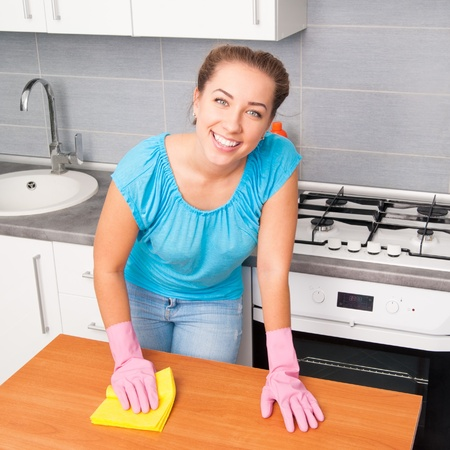housewife gloves: young cute woman cleans the kitchen at her home