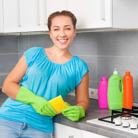 house cleaner: young smiling woman cleans the kitchen Stock Photo