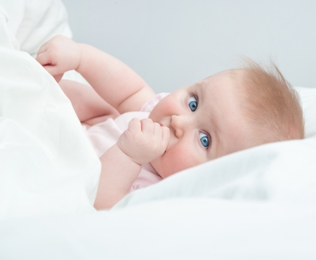 only child: beautiful baby sucks his thumb lying in bed