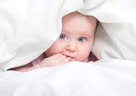 cute baby under a blanket in bed photo