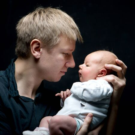 Portrait of a young father and his newborn baby daughter photo