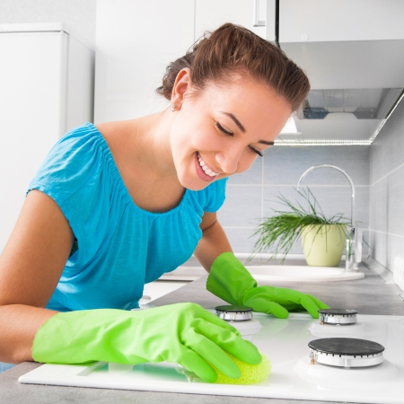 clean kitchen: smiling pretty woman cleans the kitchen at her home