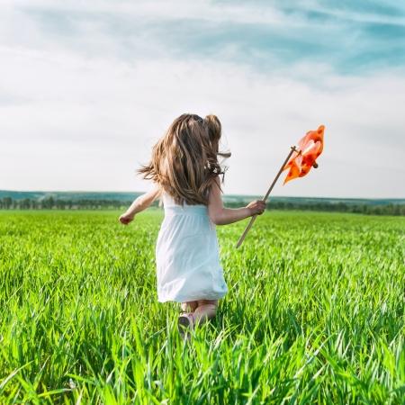 menina bonito na grama no dia de verão tem moinho de vento na mão Imagens