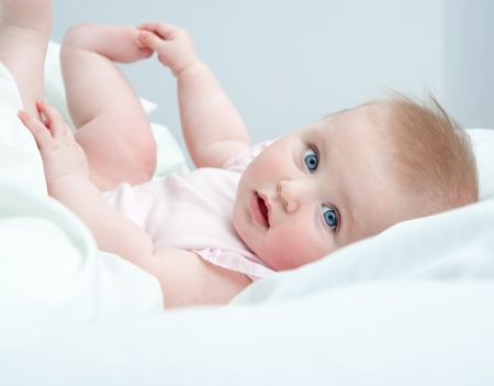 6 12 months: Happy blue-eyed baby playing with his feet on the bed at home Stock Photo