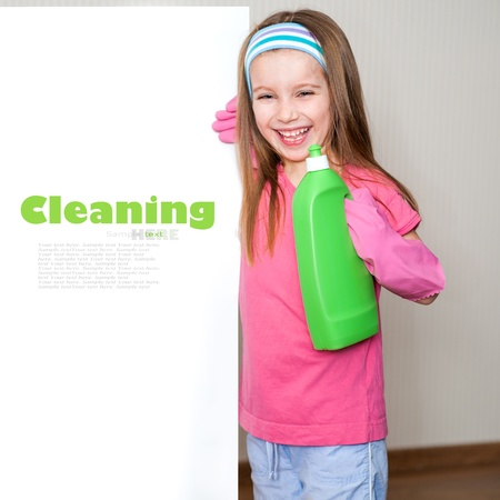 little girl holding colorful detergents and looks out from behind a banner photo