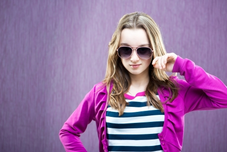 portrait of a beautiful little fashion model in sunglasses on purple background photo